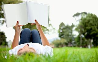 Woman lying down outdoors reading a book.jpeg