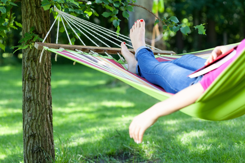 Young lady resting on hammock with book summer.jpeg
